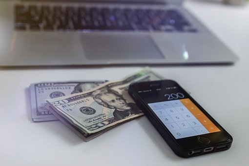 dollars, iphone and laptop