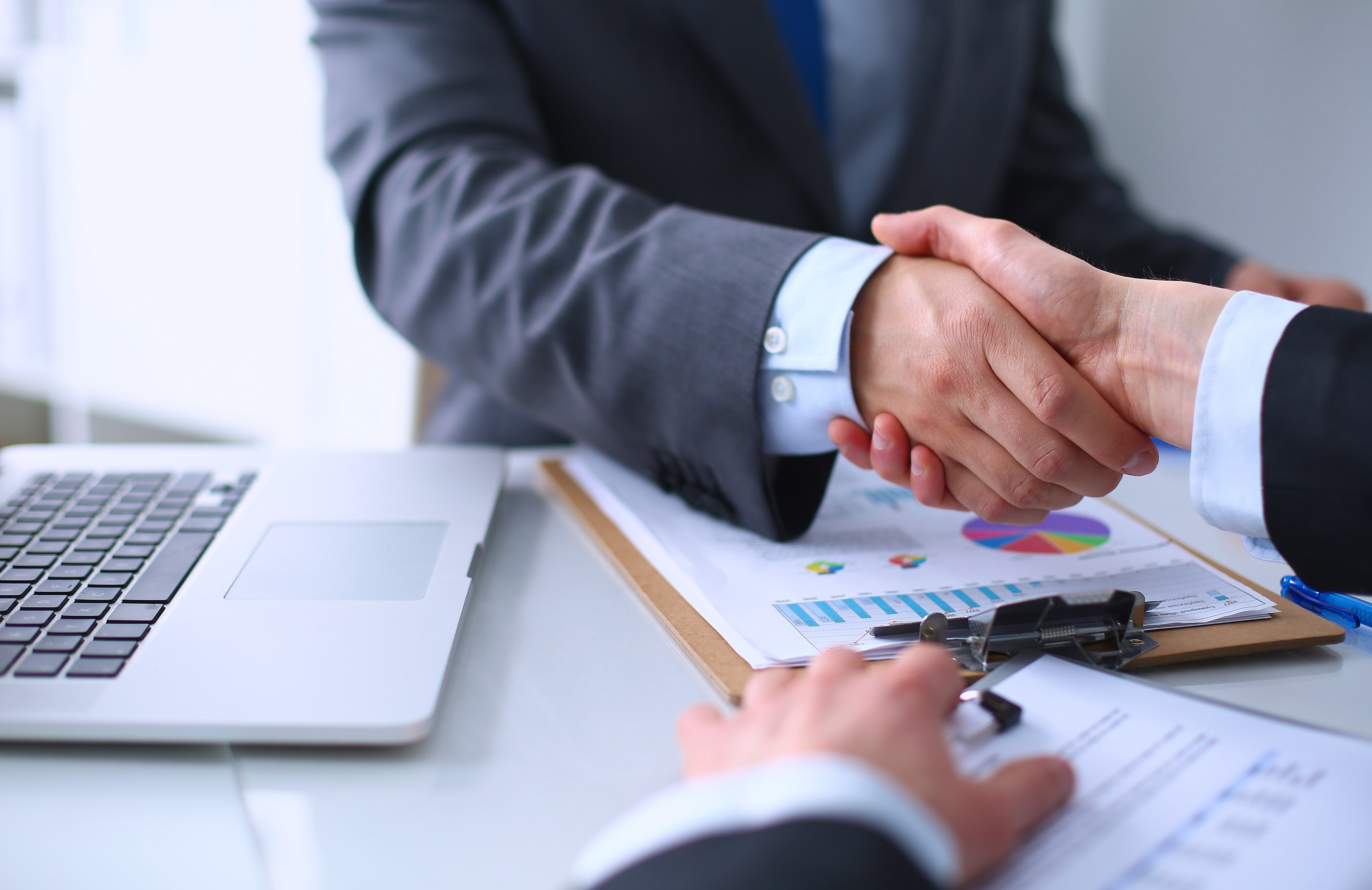 two people shaking hands over a desk with a laptop and printed financial reports representing successful purchasing of bonds from an underwriter