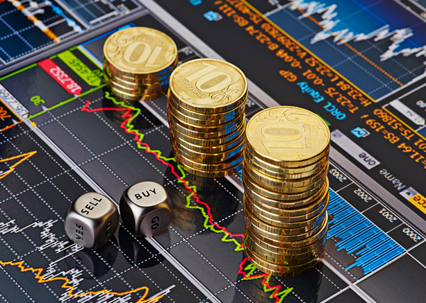 a graphic of 3 piles of gold coins stacked-up next to each other next to two silver dice that have both Sell and Buy facing upwards all on top of stock market display screen representing how to sell a business