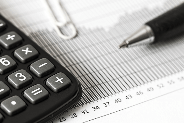 a calculator, financial report with a paper clip and a ball point pen that represents a what a financial advisor should do in providing community members with financial advice