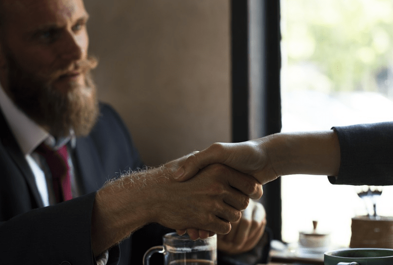 Two person shaking hands this is what Arbitration is all about, means resolving conflicts between two or more parties