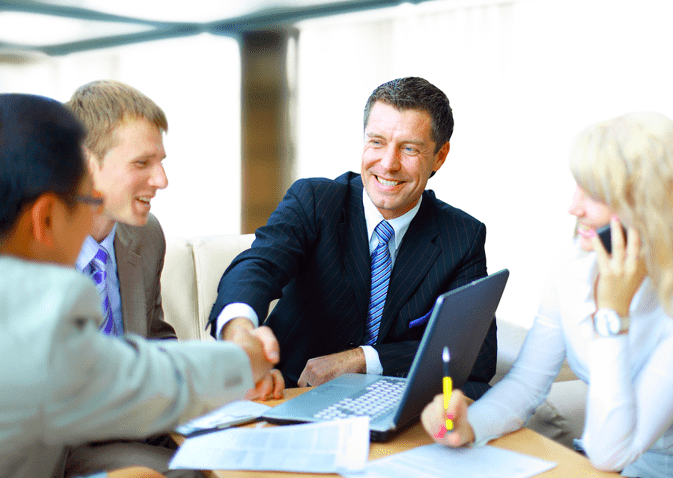 a group of four people seated in suits with a financial advisor in the center shaking hands with another person.